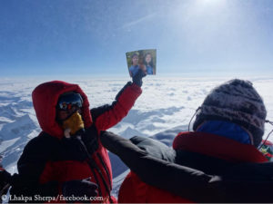 Lhakpa on Everest summit with a picture of her daughters (in 2017)